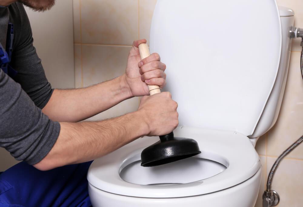 Plumber using plunger on toilet.