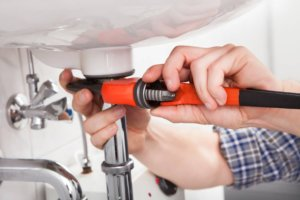 plumber fixing a sink in bathroom