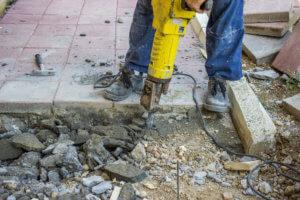 Builder worker with jackhammer repairing sidewalk crack
