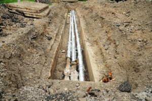 Breakthrough sewerage system.Pipes for water in an earthen trench. Repair and replacement of sewer.