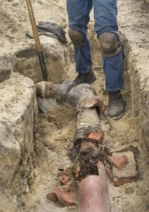 plumber is breaking apart a clay sewer line