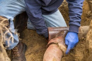 Man cleaning a clogged sewer line