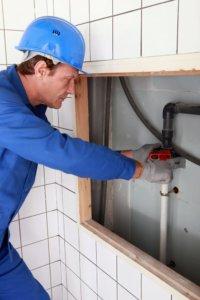 Plumber tightening a pipe
